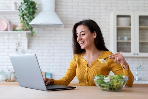 Donna che controlla computer portatile e che mangia insalata