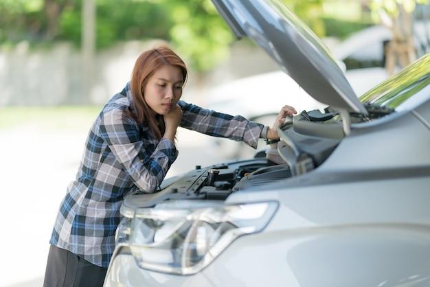 Donna che controlla il livello dell'olio in una macchina, cambia la macchina dell'olio