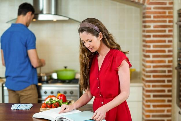 Donna che controlla il ricettario in cucina mentre uomo che cucina sulla stufa
