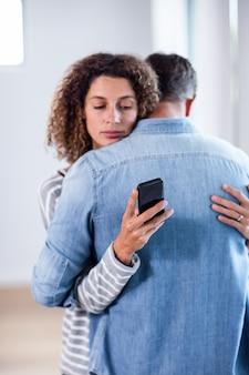 Donna che controlla il suo telefono cellulare mentre abbraccia un uomo