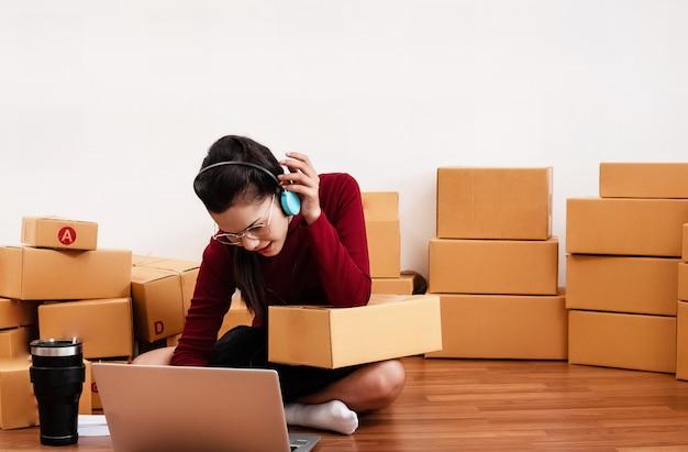 Donna che controlla ordine dal computer portatile, ufficio di lavoro a casa, piccolo imprenditore