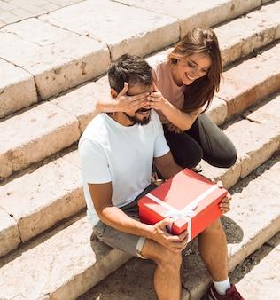 Donna che copre gli occhi del suo ragazzo e lo sorprende con un regalo