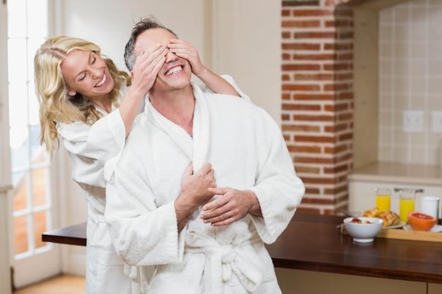 Donna che copre i suoi occhi del marito in cucina