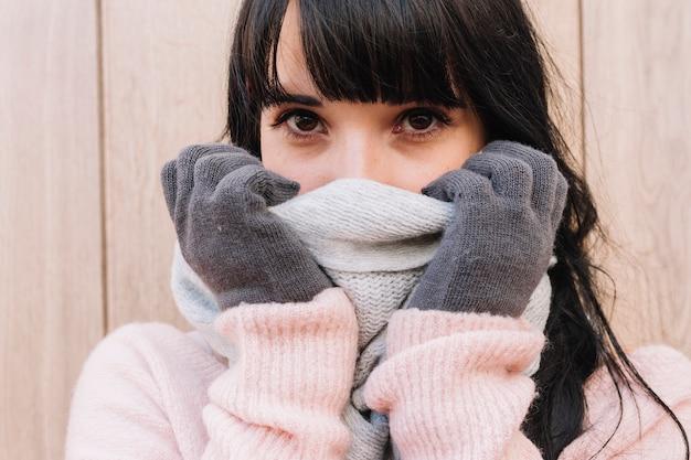 Donna che copre il naso con la sciarpa