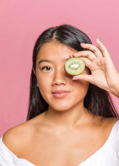 Donna che copre il suo occhio di kiwi e che guarda l'obbiettivo