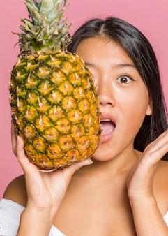 Donna che copre il viso con ananas a grandezza naturale