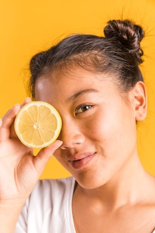 Donna che copre il viso con il limone