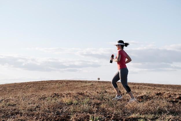 Donna che corre attraverso la campagna al tramonto