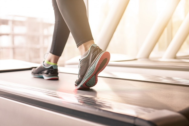 Donna che corre in una palestra su un concetto di tapis roulant per l'esercizio, la forma fisica e lo stile di vita sano