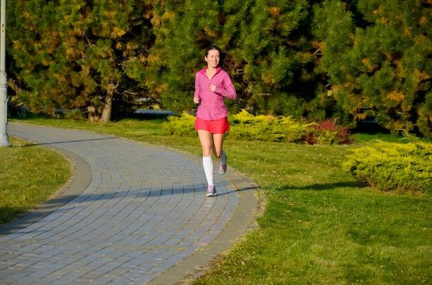Donna che corre nel parco di autunno, bello corridore della ragazza che pareggia all'aperto. concetto di esercizio e fitness