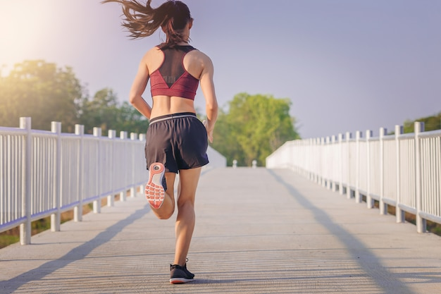 Donna che corre sprint sulla strada. fit corridore fitness femminile durante l'allenamento all'aperto