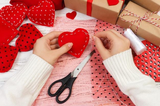 Donna che crea cuore rosso sulla tavola di legno. regalo per san valentino fatto a mano