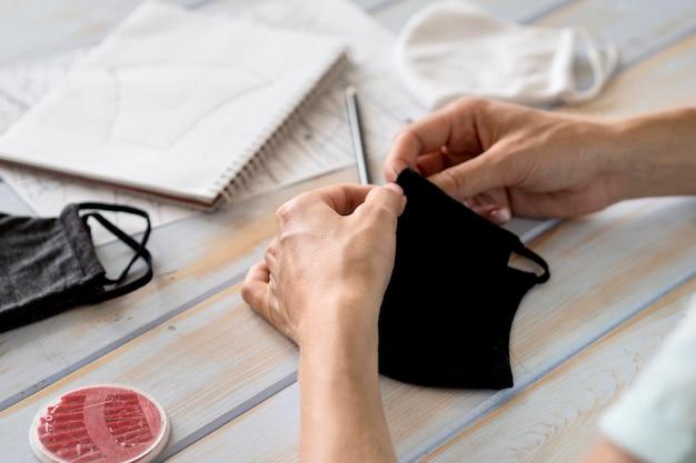 Donna che cuce la maschera per il viso manualmente