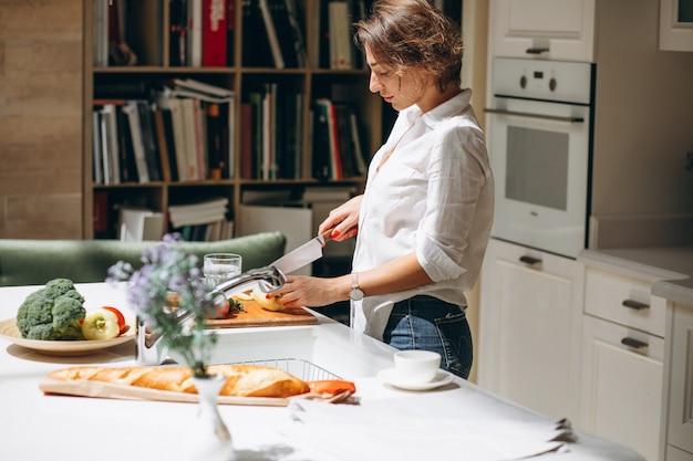 Donna che cucina alla cucina di mattina