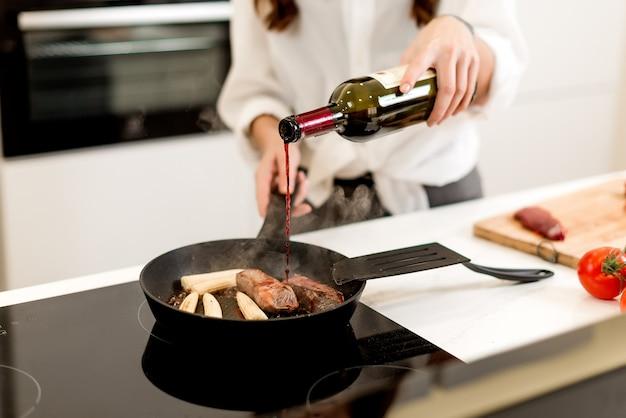 Donna che cucina carne con vino in padella con il vapore sulla cucina