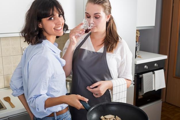 Donna che cucina cibo guardando fotocamera in piedi vicino ai bicchieri di vino in cucina