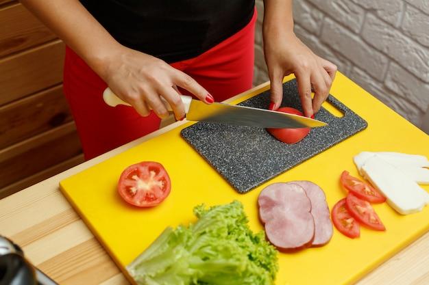 Donna che cucina dagli ortaggi freschi