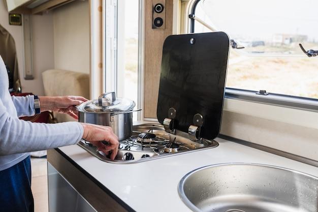 Donna che cucina dentro una casa mobile