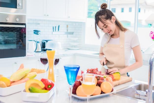 Donna che cucina e affettare verdura nella stanza della cucina con pieno di cibo e frutta sul tavolo