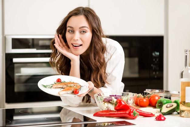 Donna che cucina il piatto di pesce alla cucina
