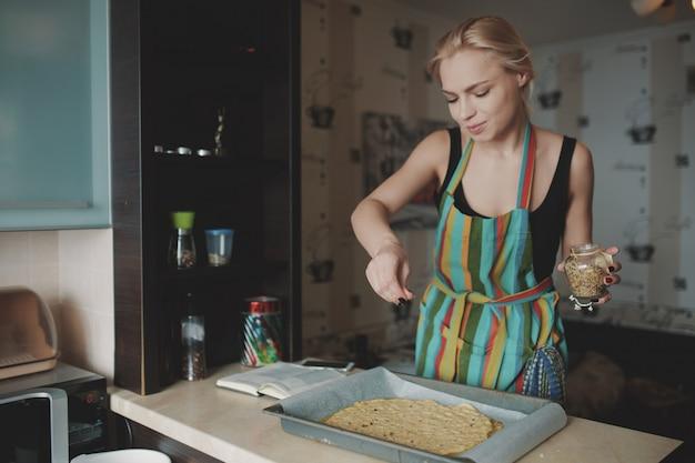 Donna che cucina pizza in cucina