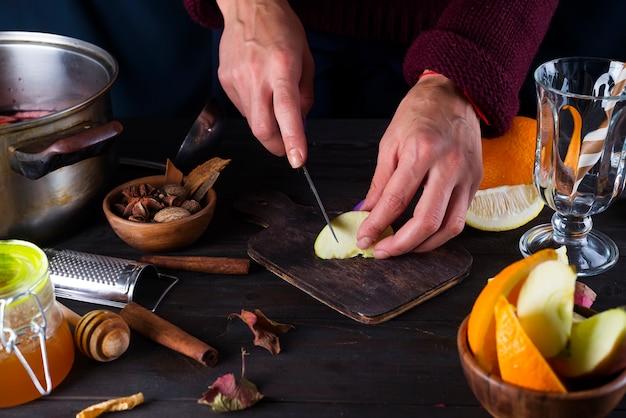 Donna che cucina vin brulé in cucina
