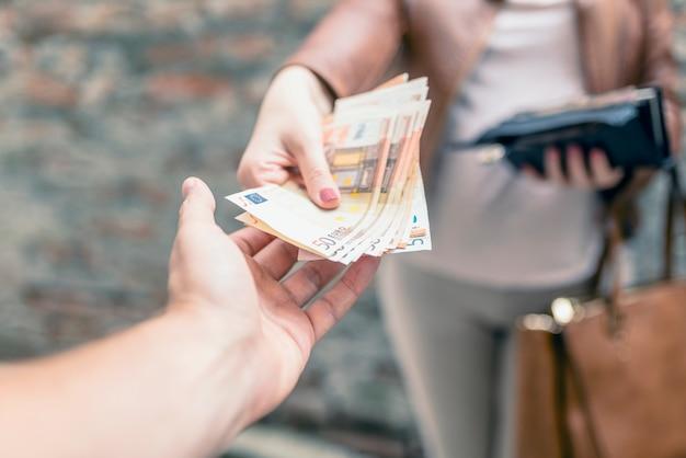 Donna che dà soldi a un uomo. mano che riceve il denaro. ricevere una tangente