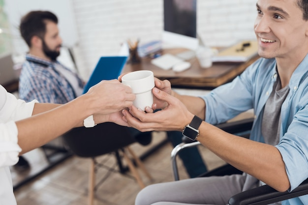 Donna che dà tazza all'uomo sulla sedia a rotelle in ufficio.