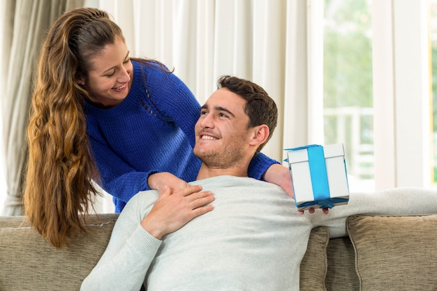 Donna che dà un regalo a sorpresa al suo uomo a casa