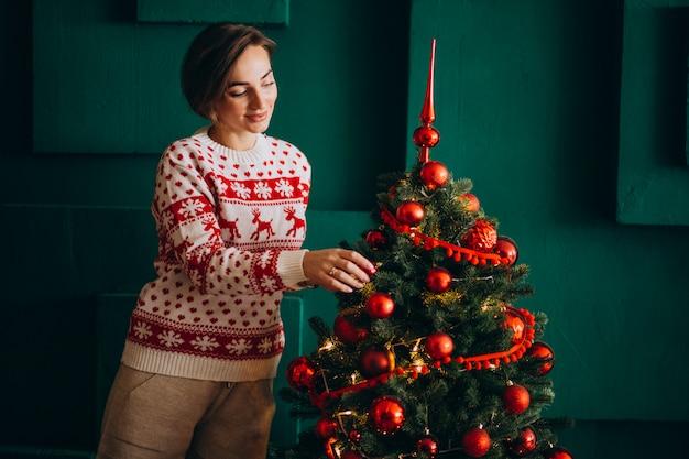 Donna che decora l'albero di natale con i giocattoli rossi