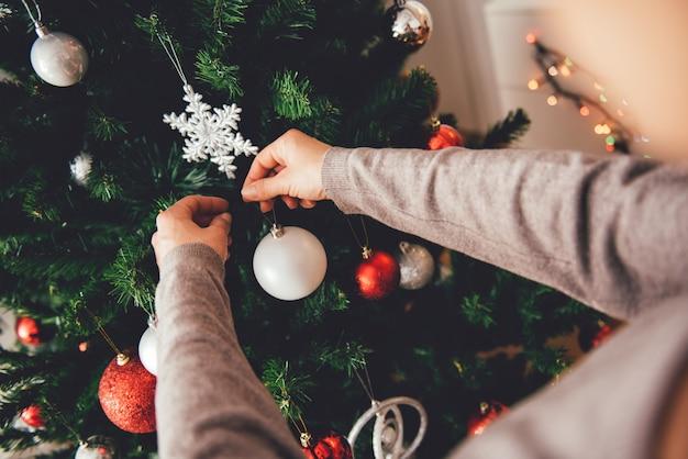 Donna che decora un albero di natale