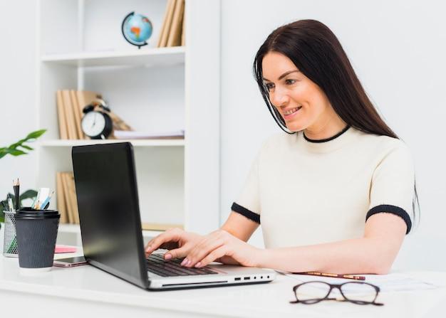 Donna che digita sulla tastiera del computer portatile al tavolo