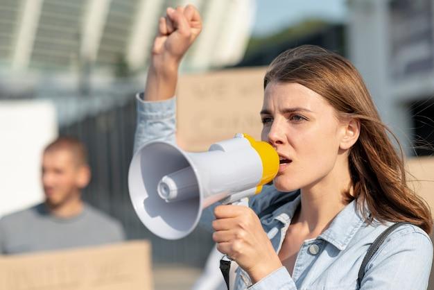 Donna che dimostra con il megafono