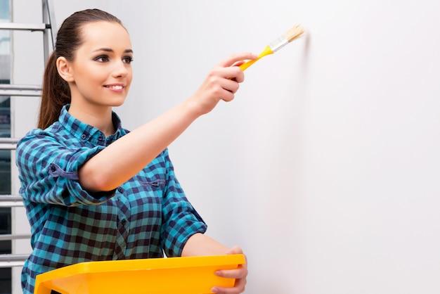 Donna che dipinge la parete nel concetto di diy