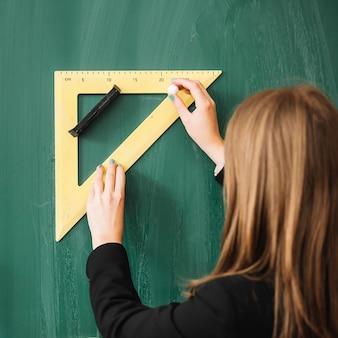 Donna che disegna con il righello triangolare sulla lavagna