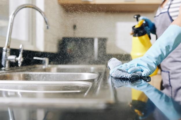 Donna che disinfetta il bancone della cucina