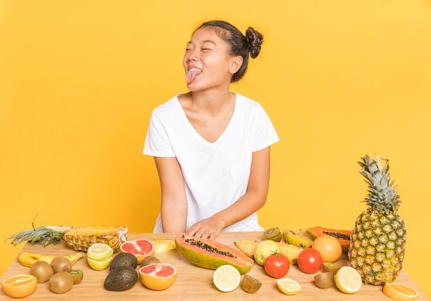 Donna che distoglie lo sguardo dietro una tavola con i frutti