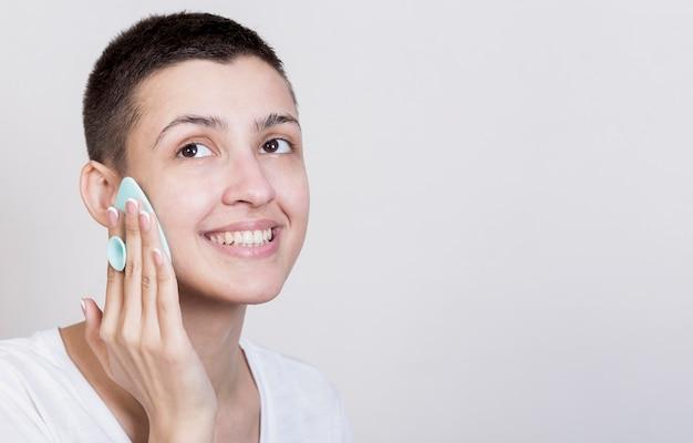 Donna che distoglie lo sguardo processo di pulizia del viso