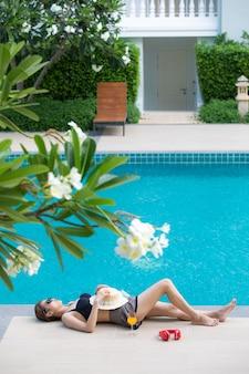 Donna che dorme accanto alla piscina