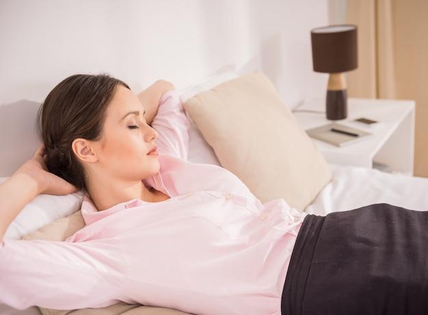 Donna che dorme sul letto dopo una dura giornata di lavoro.