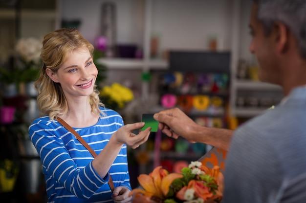 Donna che effettua pagamento con la sua carta di credito al fiorista