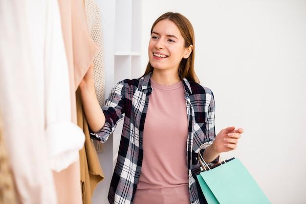 Donna che esamina i vestiti con le borse in sua mano
