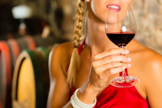 Donna che esamina il vetro del vino rosso in cantina
