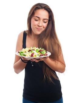 Donna che esamina la sua insalata con dessire