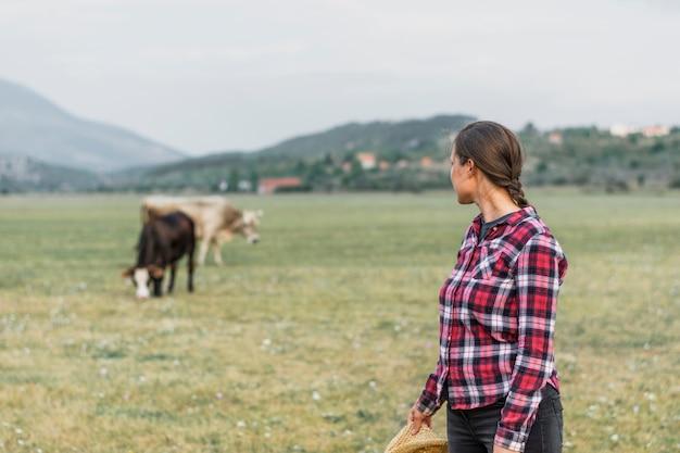 Donna che esamina le mucche di pascolo nel campo