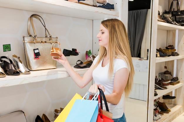 Donna che esamina le scarpe nel negozio di scarpe