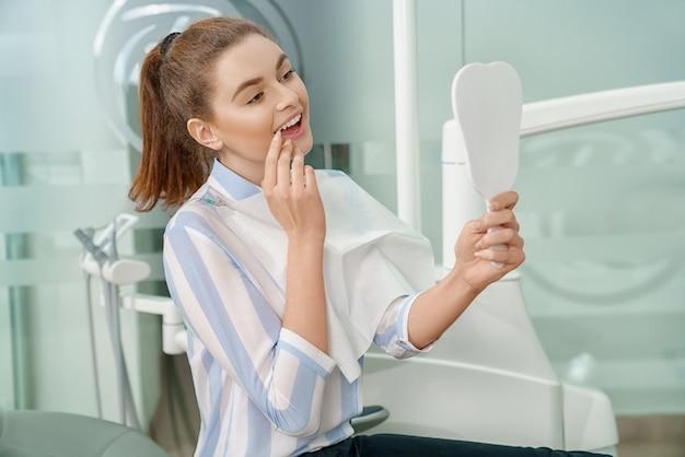 Donna che esamina specchio e che gode del sorriso in studio dentistico