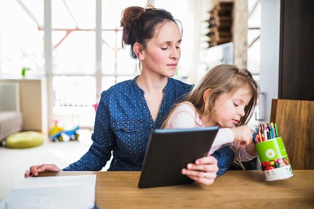 Donna che esamina sua figlia che sceglie matita mentre tenendo compressa digitale