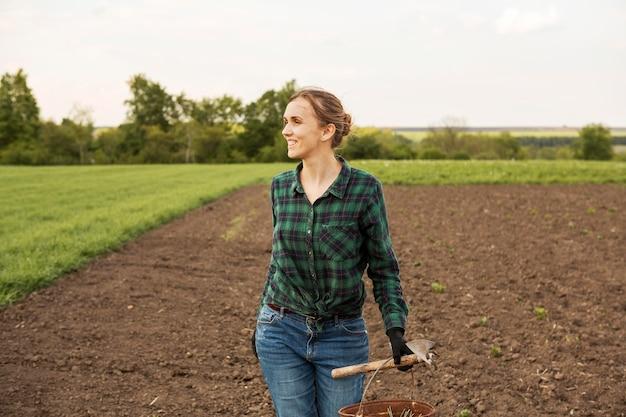 Donna che esamina una terra coltivata