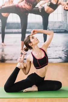 Donna che esegue allungando esercizio nello studio di forma fisica sulla stuoia verde di esercizio